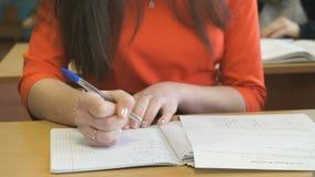 La scolara che si siede allo scrittorio impara le lezioni stock footage