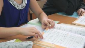 La scolara che si siede allo scrittorio lancia le pagine del libro archivi video