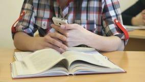La scolara che si siede allo scrittorio scrive il testo in quaderno archivi video