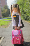 La scolara con una cartella pesante fotografie stock
