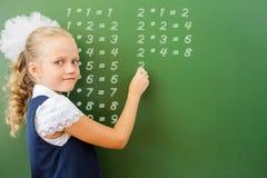 La scolara del primo grado ha scritto la tavola di moltiplicazione sulla lavagna con gesso Fotografia Stock