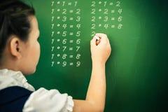 La scolara del primo grado ha scritto la tavola di moltiplicazione sulla lavagna con gesso Immagine Stock