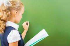 La scolara del primo grado ha scritto sulla lavagna con gesso all'aula Immagine Stock