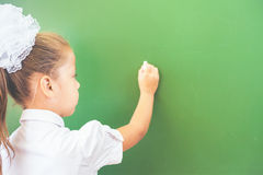 La scolara del primo grado ha scritto sulla lavagna con gesso all'aula Immagini Stock Libere da Diritti