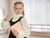 La scolara della ragazza con un libro a disposizione mostra il pollice Immagini Stock Libere da Diritti