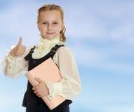La scolara della ragazza con un libro a disposizione mostra il pollice Fotografie Stock