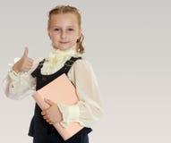 La scolara della ragazza con un libro a disposizione mostra il pollice Immagini Stock