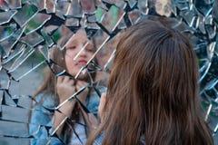 La scolara della ragazza esamina uno specchio rotto e soffre e mostra sulla gola fotografia stock