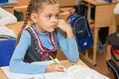 La scolara della ragazza si siede ad uno scrittorio della scuola alla lezione alla scuola Fotografia Stock Libera da Diritti