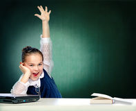 La scolara fa le lezioni che si siedono dietro uno scrittorio Fotografia Stock