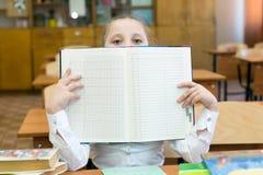 La scolara ha coperto il suo fronte di gradebook della scuola immagine stock