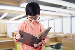 La scolara legge il libro nella sala di lettura Immagine Stock