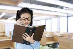 La scolara legge il manuale in aula Fotografia Stock