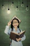 La scolara ottiene l'ispirazione con la lampadina Fotografie Stock