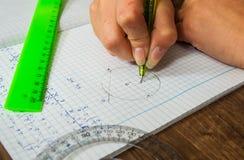La scolara risolve il problema di matematica Immagini Stock