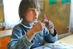 La scolara rurale si siede ad uno scrittorio della scuola in aula s elementare Fotografia Stock Libera da Diritti