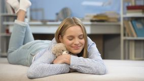 La scolara sorridente che abbraccia il suo orsacchiotto gioca in camera da letto, la comodità domestica di infanzia video d archivio