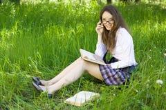 La scolara in sosta ha letto il libro Fotografia Stock