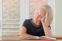 La scolara stanca del bambino dorme durante la lezione allo scrittorio in un'aula Fotografia Stock