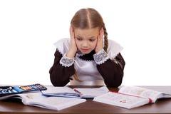 La scolara triste si siede ad uno scrittorio della scuola Immagini Stock Libere da Diritti