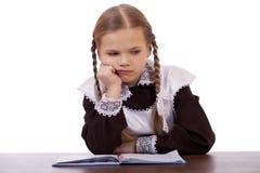 La scolara triste si siede ad uno scrittorio della scuola Immagine Stock Libera da Diritti