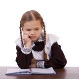 La scolara triste si siede ad uno scrittorio della scuola Fotografie Stock