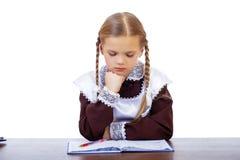 La scolara triste si siede ad uno scrittorio della scuola Immagine Stock
