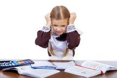 La scolara triste si siede ad uno scrittorio della scuola Fotografia Stock