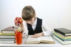 La scolara in uniforme legge il libro con la mela rossa alla tavola Fotografia Stock Libera da Diritti