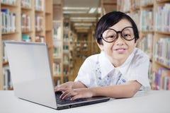 La scolara utilizza il computer portatile nella biblioteca Fotografie Stock