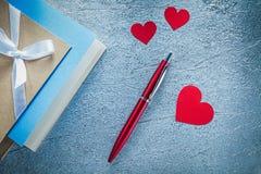 La scrittura d'annata dei cuori della penna rossa del biro prenota su fondo metallico Immagine Stock