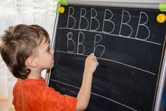 La scrittura del ragazzo segna l'apprendimento con lettere del bambino astuto del figlio dei procces Immagine Stock