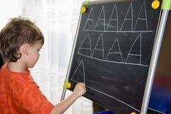 La scrittura del ragazzo segna la conoscenza con lettere dell'apprendimento di piccolo bambino Immagine Stock