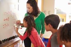 La scrittura dell'allievo sul bordo ai per la matematica della scuola elementare classifica Immagini Stock Libere da Diritti