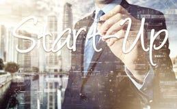 La scrittura dell'uomo d'affari comincia su sullo schermo virtuale dietro la o posteriore immagini stock libere da diritti