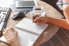 La scrittura della donna ha sparato la nota di memorie su Libro Bianco con Ti di rilassamento Fotografie Stock