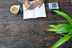 la scrittura della donna sul taccuino, sulla tazza di caffè e sul calcolatore ha messo sopra il legno Immagini Stock Libere da Diritti