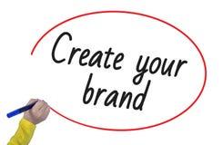 La scrittura della mano della donna crea la vostra marca con l'indicatore fotografia stock libera da diritti