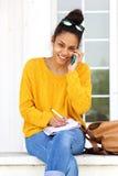 La scrittura femminile sorridente prenota e parlando sul telefono cellulare Fotografie Stock