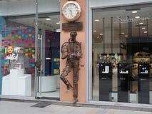 La sculpture de l'homme vérifiant le temps fait de métal réutilisé rapièce Images libres de droits