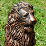 La sculpture dorée de la tête d'un lion a placé en parc Image stock