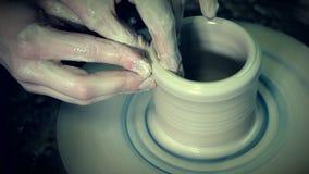 La sculpture en argile avec des mains sur un ` tournant s de potier roulent handmade banque de vidéos