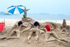 La sculpture en sable les prennent un bain de soleil sur la plage de Copacabana Photographie stock libre de droits