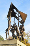 La scultura della gente che porta la bandiera olimpica fotografie stock
