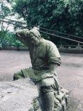 La scultura di pietra dell'agricoltore che sta ritenendo a come giocare gli scacchi fotografia stock