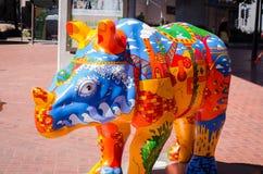 La scultura dipinta variopinta di rinoceronte del materiale illustrativo è una mostra di arte pubblica al porto caro immagine stock libera da diritti