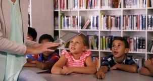 La scuola d'istruzione dell'insegnante scherza sulla compressa digitale in biblioteca stock footage