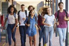 La scuola dell'adolescente scherza il funzionamento nel corridoio della High School immagini stock