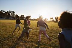 La scuola elementare scherza giocar a calcioe in un campo, vista posteriore immagine stock
