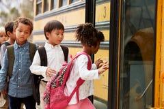 La scuola elementare scherza la scalata sopra ad uno scuolabus Immagini Stock Libere da Diritti